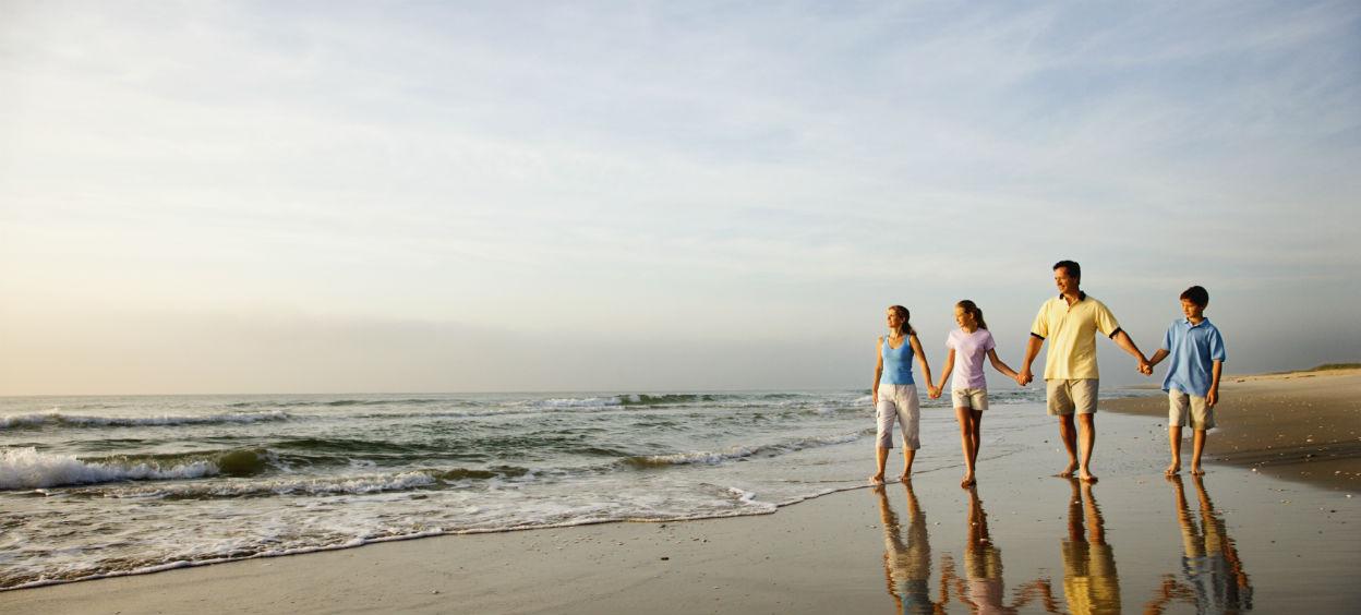 Famille qui marche ensemble sur la plage