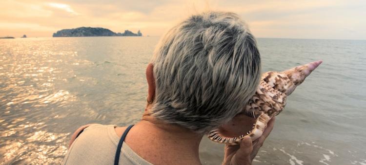 Dame âgée écoutant un coquillage sur la plage